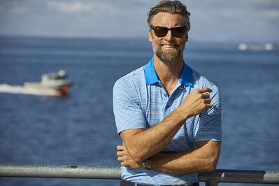 Man smiling and standing by water wearing a Cutter & Buck polo and sunglasses