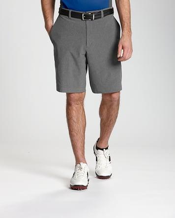 Man wearing sneakers and Cutter & Buck Bainbridge Flat Front Short in Grey