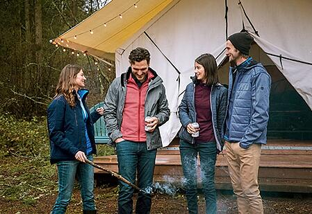 Two couples standing by a fire while glamping at Lake Dale Resort in San Juan Island, Washington