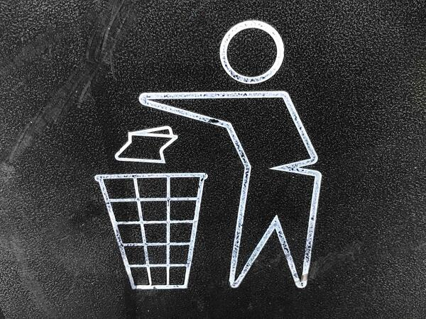Drawing of person discarding trash in a recycle bin