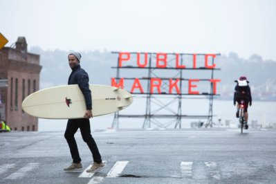 Man with surfboard wearing Cutter & Buck at Pike Place Market in Seattle