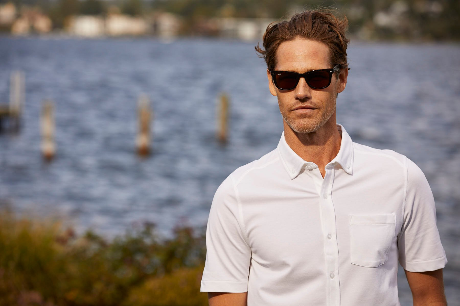 Man standing by water wearing sunglasses and white button-up polo from Cutter and Buck