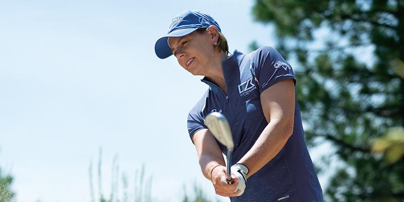 Annika hitting a golf ball wearing Cutter and Buck Annika collection.