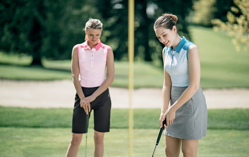 Two women playing golf wearing Cutter and Buck Sleeveless Polos