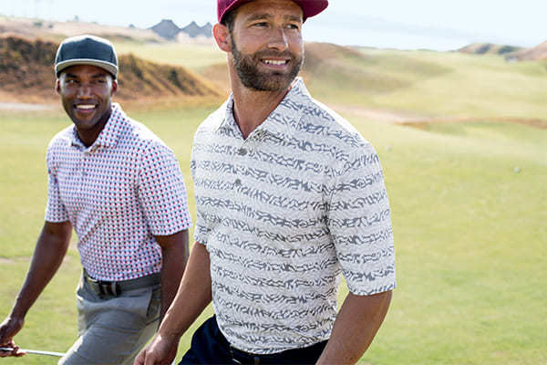 Two men smiling and golfing wearing Cutter & Buck Polos