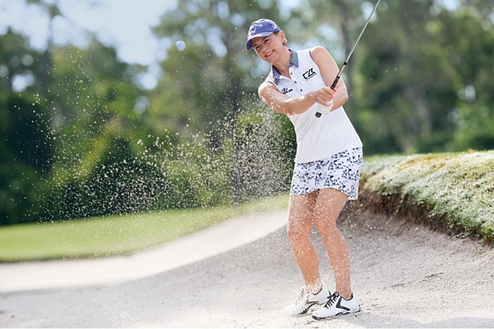 Woman playing golf wearing a Cutter and Buck womens golf skort
