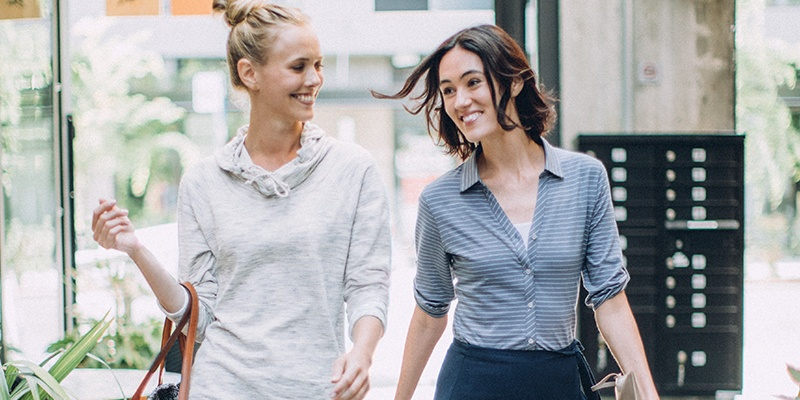 Two women walking and smiling next to each other.