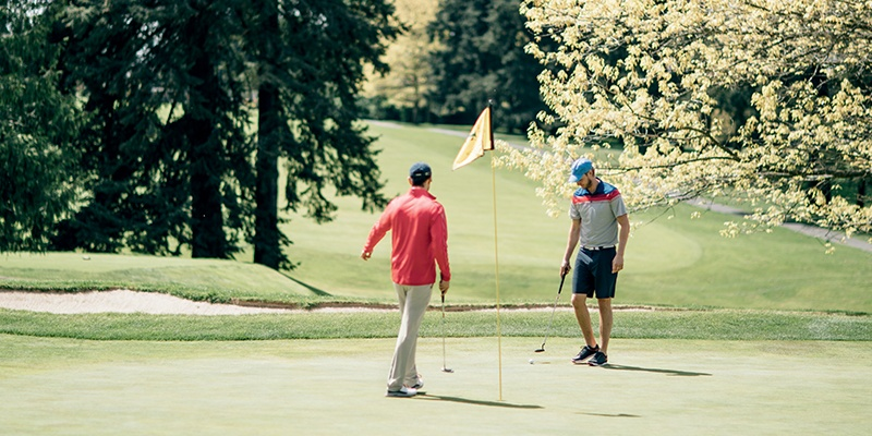 Two guys playing golf on a golf course